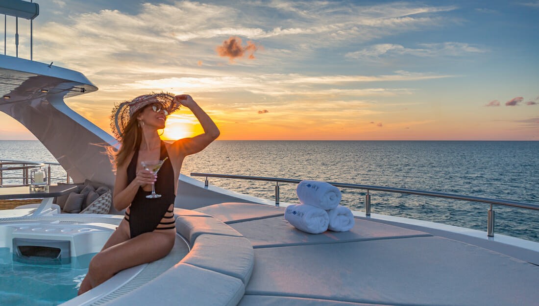 A woman on yacht Big Sky in a Jacuzzi at sunset