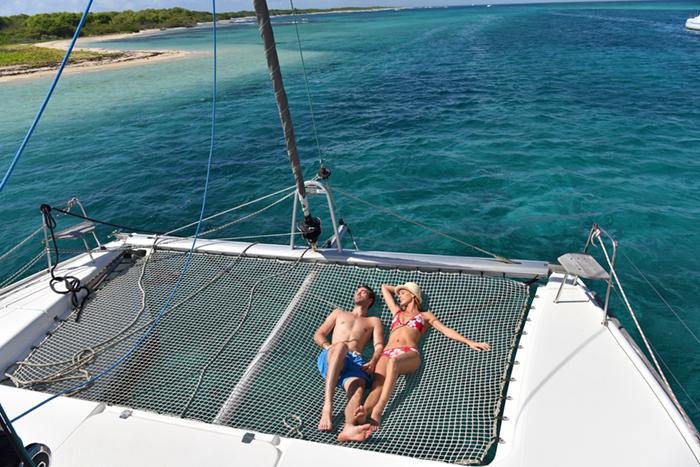 honeymoon couple sunning on a catamaran