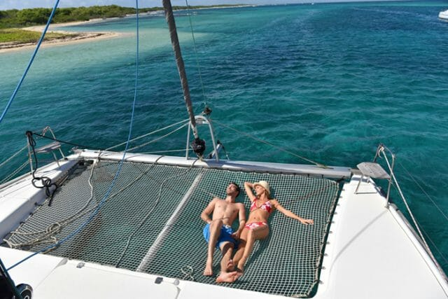 honeymoon couple sunning on a catamaran