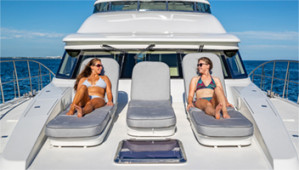 two ladies sunbathing on a bow of a yacht